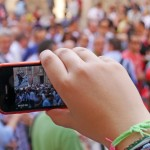 Photo of a hand holding a smartphone in front of a crowd. By Chris Brown, CC-BY-SA