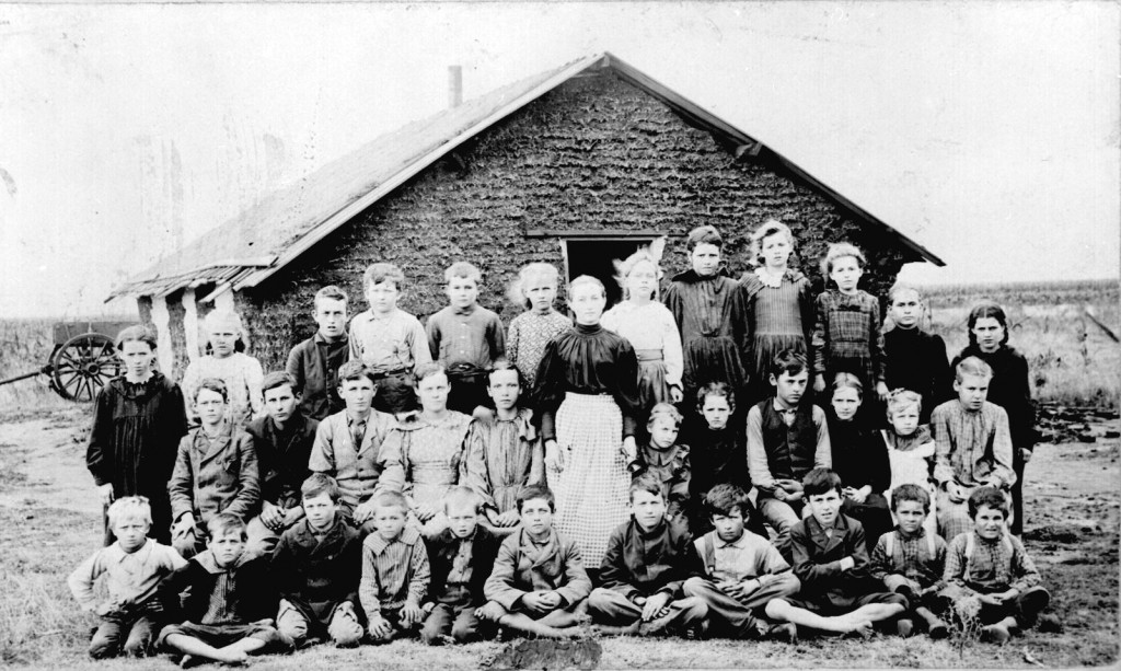 Teacher and children in front of sod schoolhouse. Woods Co., Okla. Terr., ca. 1895.