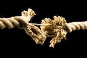 Closeup of frayed rope about to break. Isolated over black background.