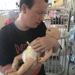 Ben Hytrek holding newborn nursing manikin