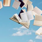 Books soaring in the sky with clouds in the background