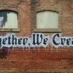 Together we create painted on a brick wall